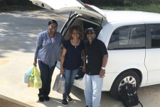 Three people holding grocery bags stand in front of a van