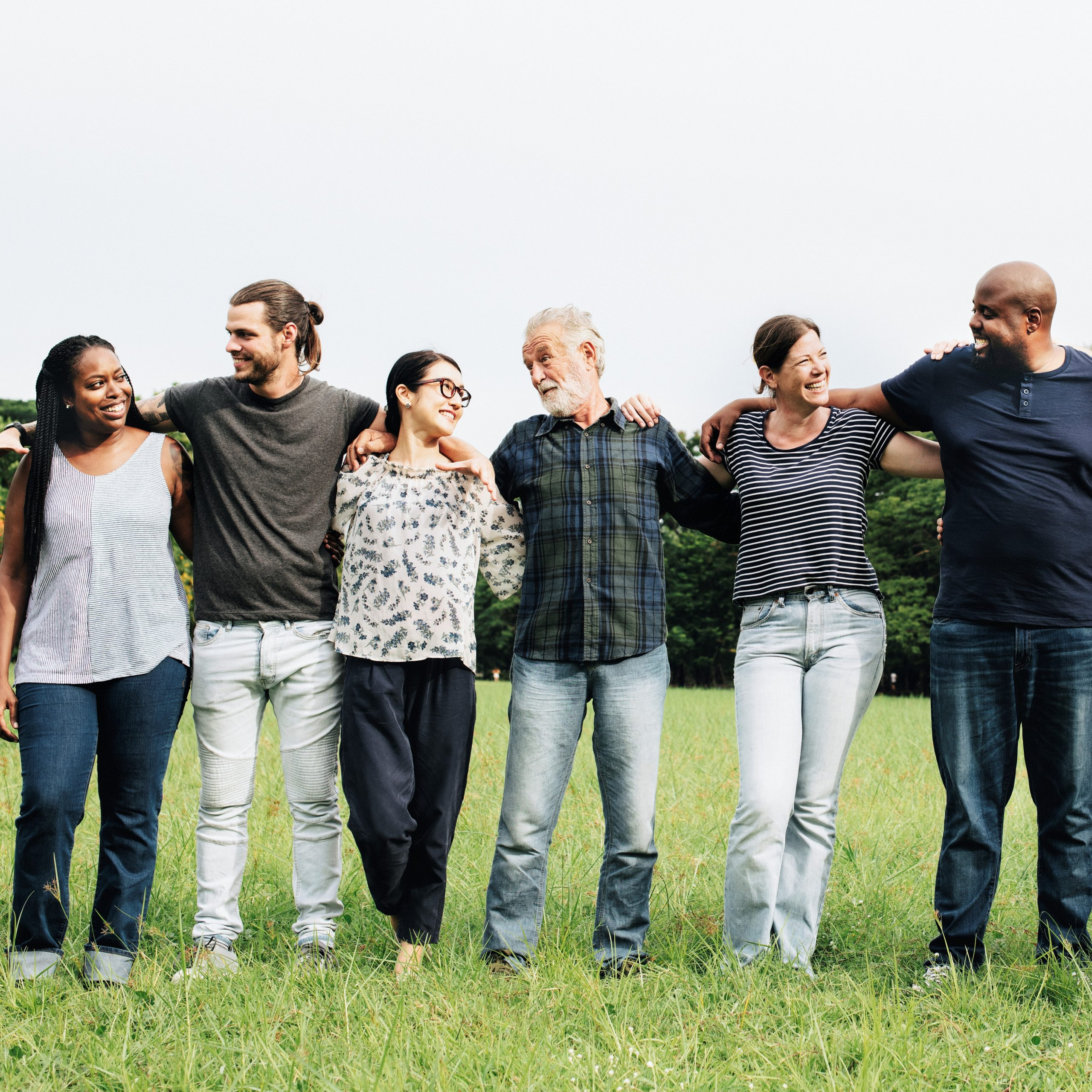 Group of people standing together with arms around each others' shoulders