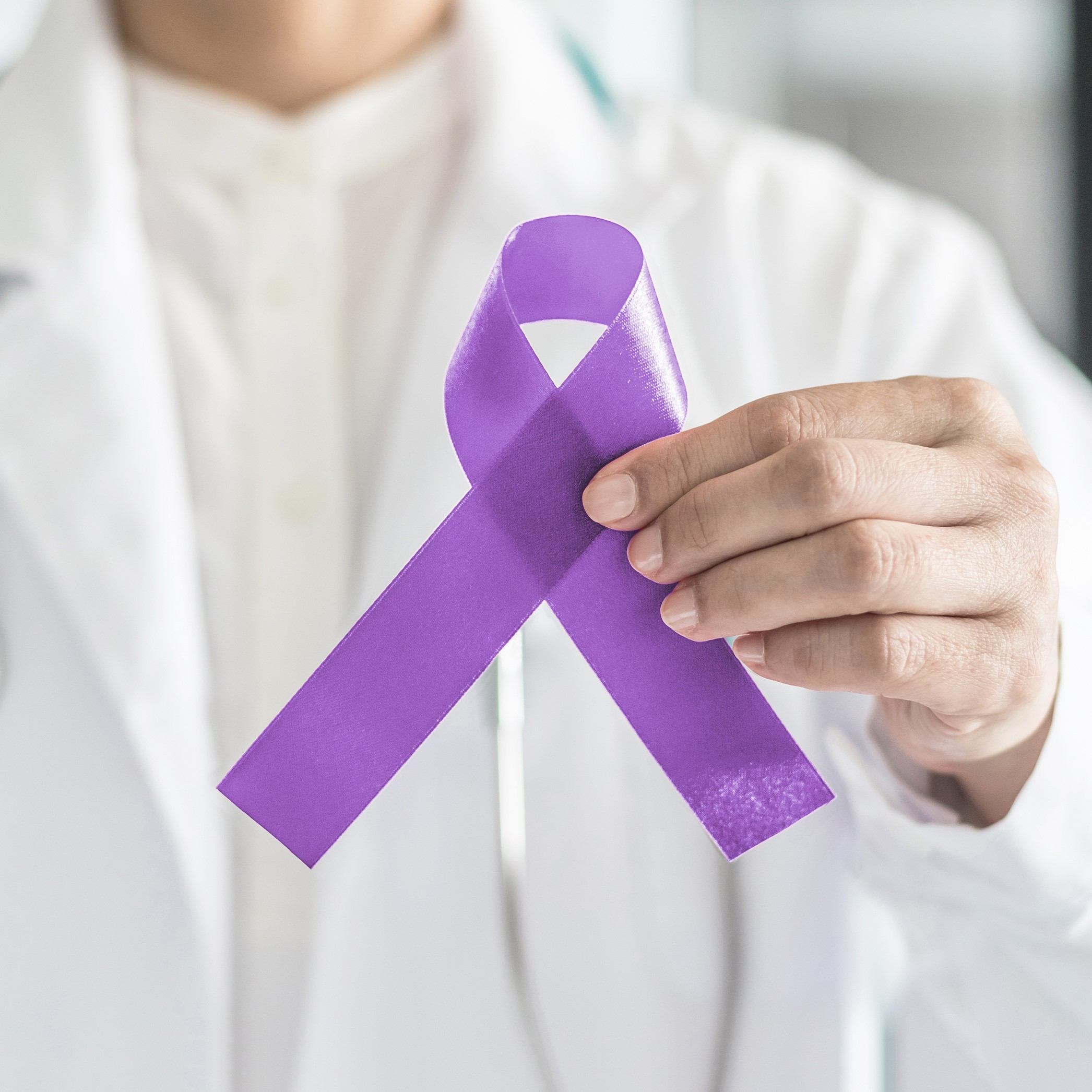 Doctor holding purple ribbon for cancer awareness
