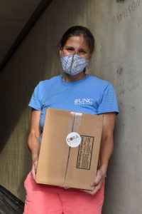 Woman wearing a mask and holding a box that says Cora Food Pantry
