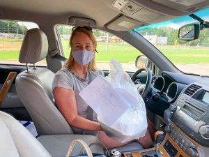 Woman wearing a surgical mask in the driver's seat of a car and holding a plastic bag of produce or meals