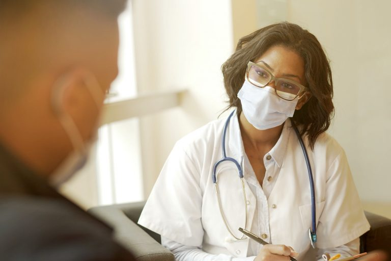 Doctor wearing mask listening to patient
